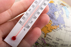 Hand placing a thermometer on a model globe Royalty Free Stock Image