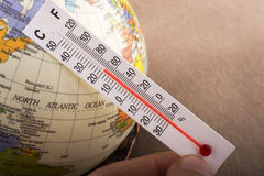 Hand placing a thermometer on a model globe Royalty Free Stock Photos