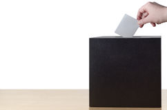 Hand Placing Voting Slip in Ballot or Suggestion Box. Hand placing folded voting slip into slot in ballot box on light wood table. Isolated on white background stock images