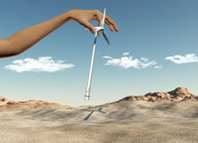 Hand placing wind turbines in a desert Stock Photography