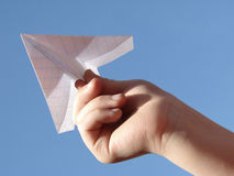 Hand with plane. Child hand with paper plane against blue sky Royalty Free Stock Image