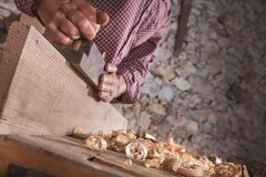 Hand plane being used to smooth wooden plank. Hand plane being used by off camera carpenter wearing plaid shirt to smooth long wooden plank royalty free stock photo
