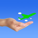 Hand and plane. Hand and green plane on blue sky background stock images