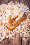 Hand planer shavings in wood. Wooden planer, table from old wood, a natural building material, handcrafted wood, ancient hand tools, carrying out carpentry Royalty Free Stock Images