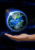 Hand holding Rising Sun over the world with north and south america. Hand with Planet earth with sunrise in space globe on it. (Elements of this image furnished royalty free stock photos