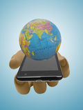 Hand of plastic mannequin doll with smartphone and Earth globe. Royalty Free Stock Photography