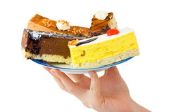 Hand and plate with cakes Royalty Free Stock Images