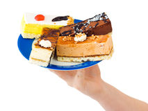 Hand and plate with cakes Royalty Free Stock Photography