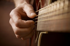 Hand playing acoustic guitar. Close up of guitarist hand playing acoustic guitar Royalty Free Stock Photos