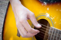 Hand playing acoustic guitar, Stock Image