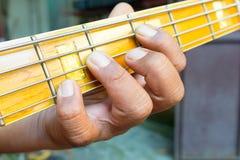 Hand playing bass. Guitar close up Stock Images