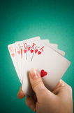 Hand and playing cards. On green background stock image