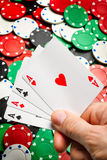 Hand with playing cards on Poker chips background Stock Images