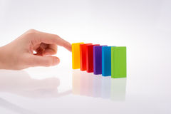 Hand playing with colored domino Royalty Free Stock Image