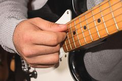 A hand playing an electric guitar with a capo royalty free stock images