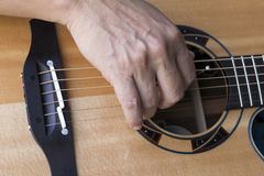 Hand playing guitar Stock Photo