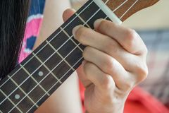 Hand playing guitar or Ukulele chord. Close up hand playing guitar or Ukulele chord., girl enjoy with her ukulele. music concept. teaching concept. relax Stock Photos