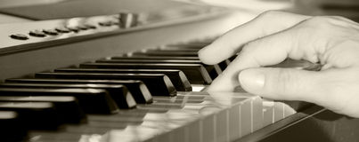 Hand playing keyboard. Black and white wide angle view of hand playing notes on electronic keyboard Royalty Free Stock Image