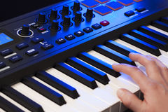 Hand Playing a MIDI Keyboard. Close up of a hand playing a MIDI controller keyboard Royalty Free Stock Photos