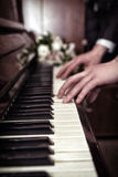 Hand playing music on the piano Stock Images