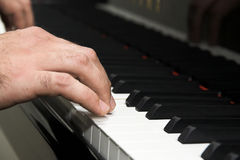 Hand playing piano Stock Photos