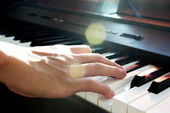 Hand playing piano. Stock Photos