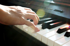 Hand playing piano. Male's hand playing piano  with light trough and flare light Royalty Free Stock Photos