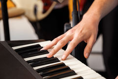 Hand Playing Piano In Recording Studio. Closeup of hand playing piano in recording studio Stock Image