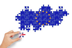 Hand plays puzzle with flag of England and EU Stock Image