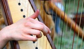 Hand while plucking the strings of a harp. Girl's hand while plucking the strings of a celtic harp royalty free stock photography