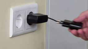 Hand plug charger adapter into wall socket. stock video