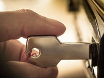 Hand plugging a key shaped USB drive into port Royalty Free Stock Photo