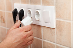 Hand plugging power cord into wall outlet Royalty Free Stock Photography