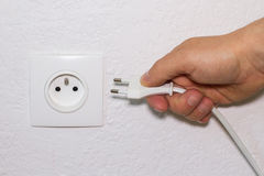 Hand plugs cord in socket Royalty Free Stock Images