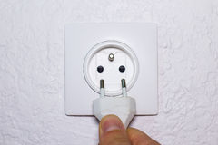 Hand plugs cord in socket Stock Images