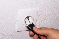 Hand plugs cord in socket Stock Image
