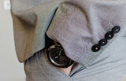 Hand in the pocket. With the black watch Stock Image