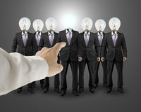 Hand point out one businessman with lighting bulb head Royalty Free Stock Image
