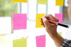 Hand point sticky note reminder on glass window. royalty free stock photos