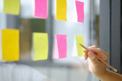 Hand point sticky note reminder on glass windows in business off. Ice stock photo