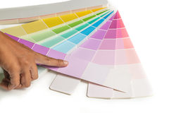 A hand point to colored swatches for choose paint sample on the white background Stock Image