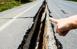 Hand point to cracked road, cracked road aftetr earthquake Stock Images