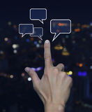 Hand point to social chat sign and speech bubbles over blur ligh. T city tower background, Social network concept Stock Photos