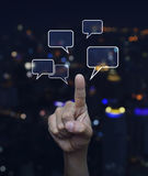 Hand point to social chat sign and speech bubbles over blur ligh. T city tower background, Social network concept Stock Image