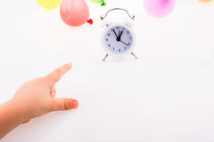 Hand pointing an alarm clock  with baloons around Royalty Free Stock Photos