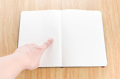 Hand pointing on blank open notebook lay it on wooden table,Temp Royalty Free Stock Images