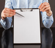 Hand pointing at blank paper in clipboard with a pen Royalty Free Stock Images