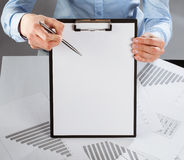 Hand pointing at blank paper in clipboard with a pen Royalty Free Stock Image