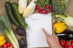 Hand pointing on book with vegetables surface Royalty Free Stock Images