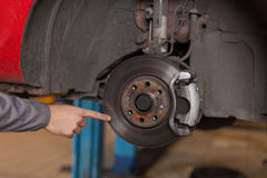 Hand pointing at car brake disc Royalty Free Stock Photography